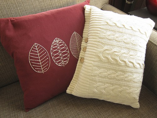 red pillow with leaves and white cable knit pillow