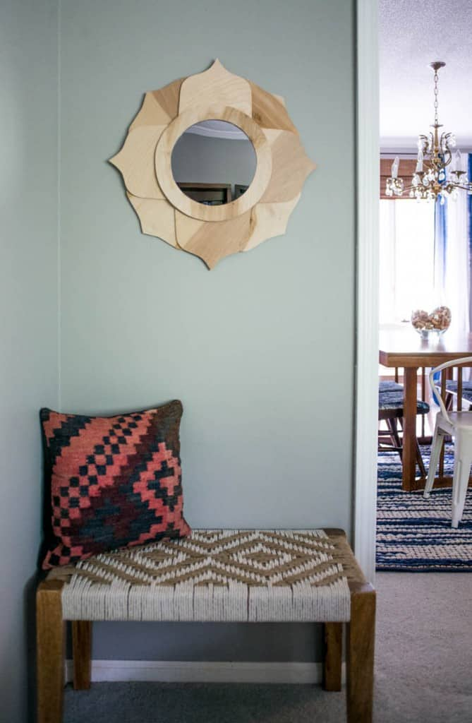 wood floral frame mirror on blue wall