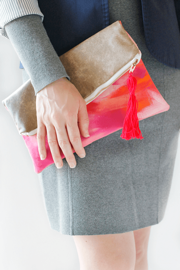 womans hand holding foldover pink and gold zippered clutch