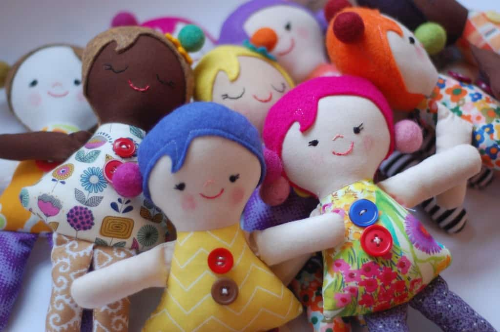 diverse stuffed dolls wearing colorful dresses