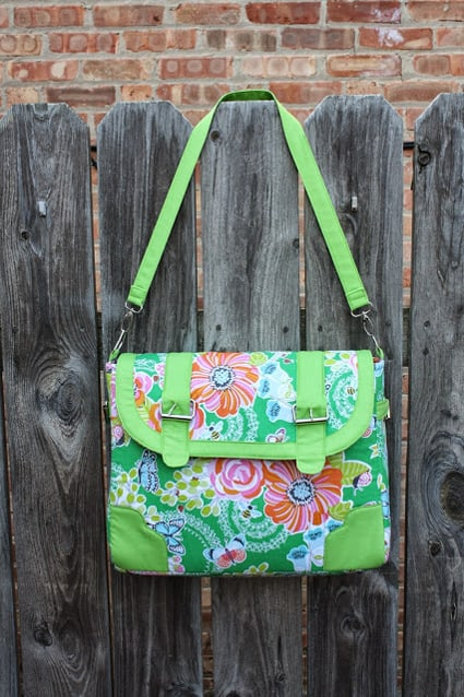 green floral purse with buckles hanging on a wood fence