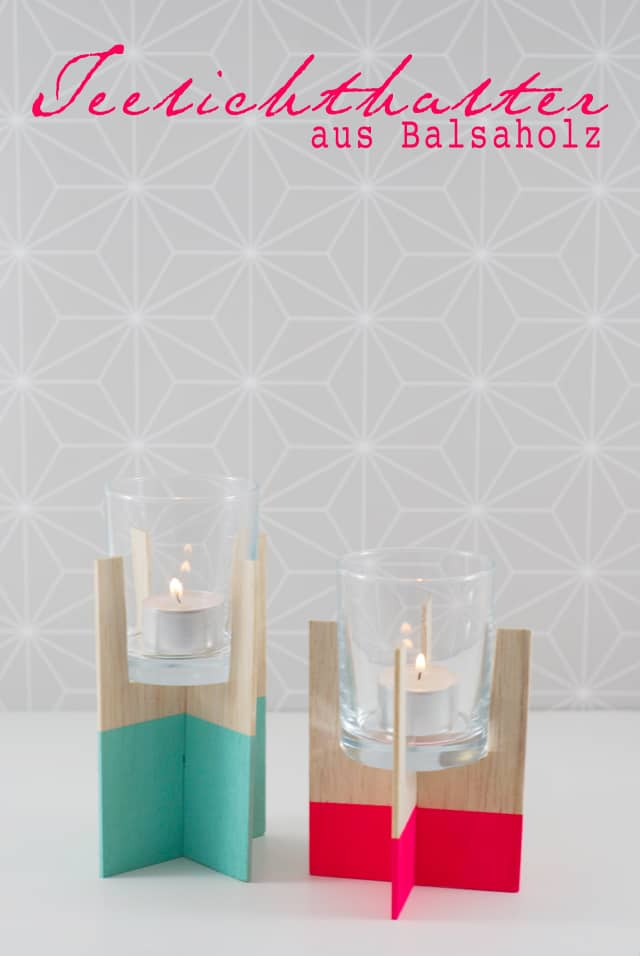 two candle holders made from crossed slabs of wood