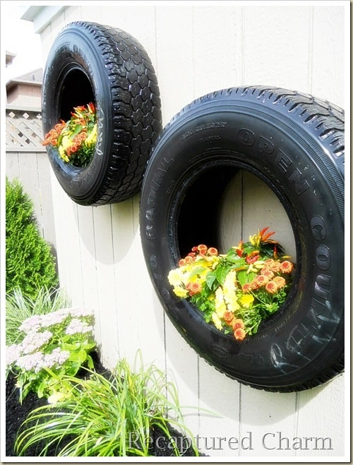 two tires hanging on a wall and planted with flowers