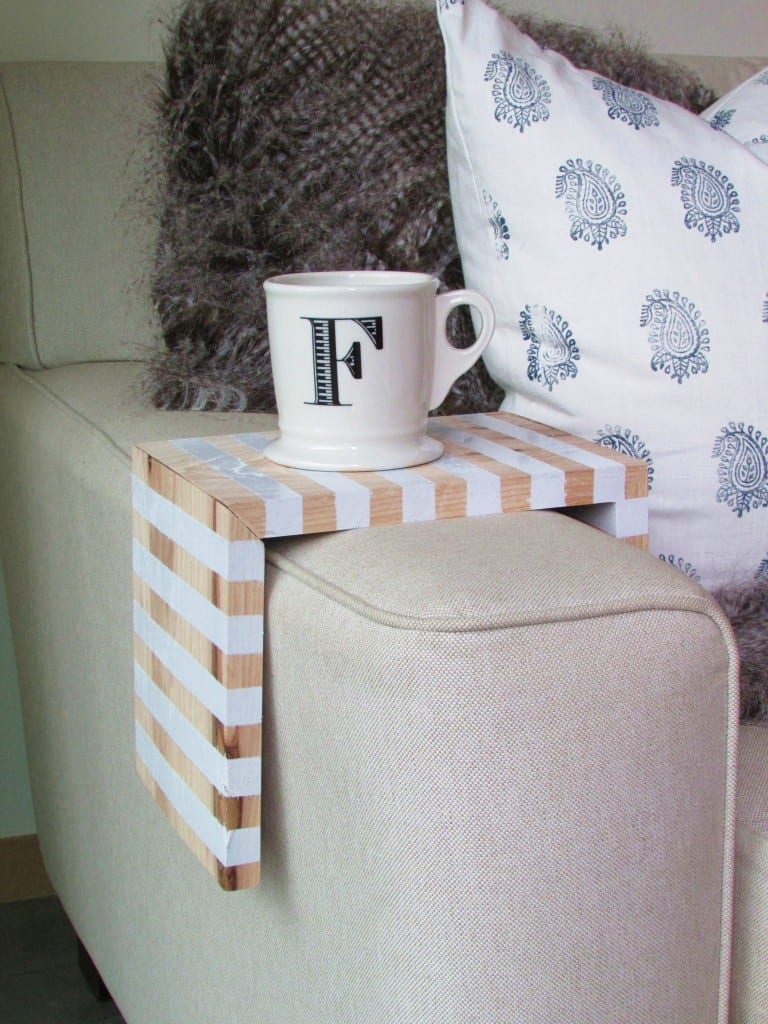 couch arm with wood shelf over holding a mug