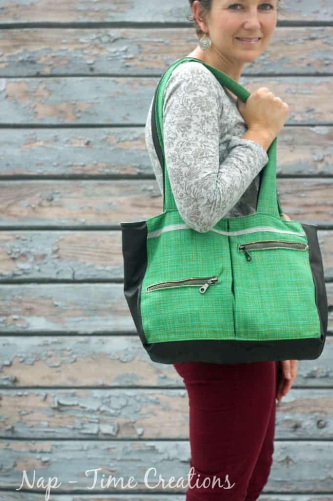 woman holding green purse with zippers