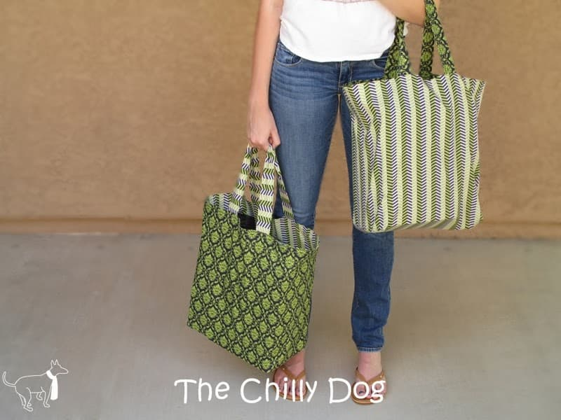 woman holding two green fabric shopping tote bags