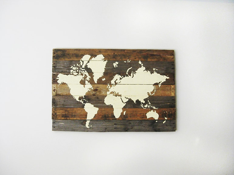 wood plank wall art with world map painted on it