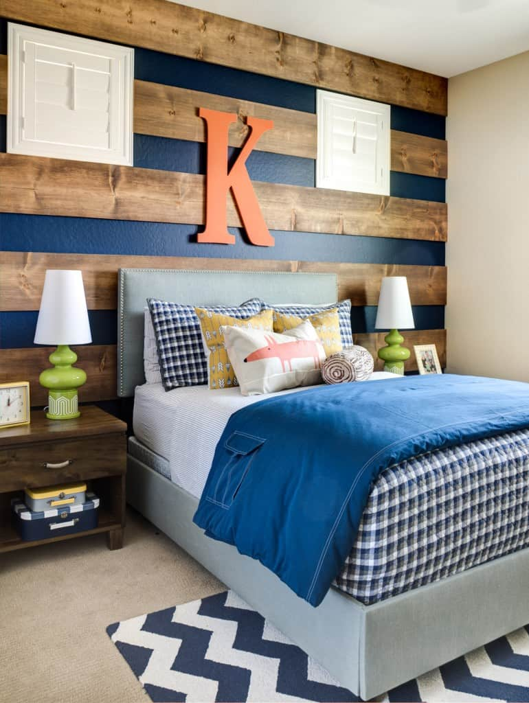 Bedroom with wall that has wood and navy stripes