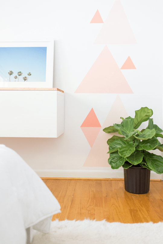 Wall mural with variously sized pink triangles on it