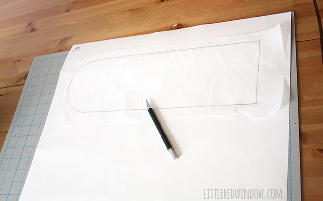 shape of door inset drawn on a piece of paper and a craft knife