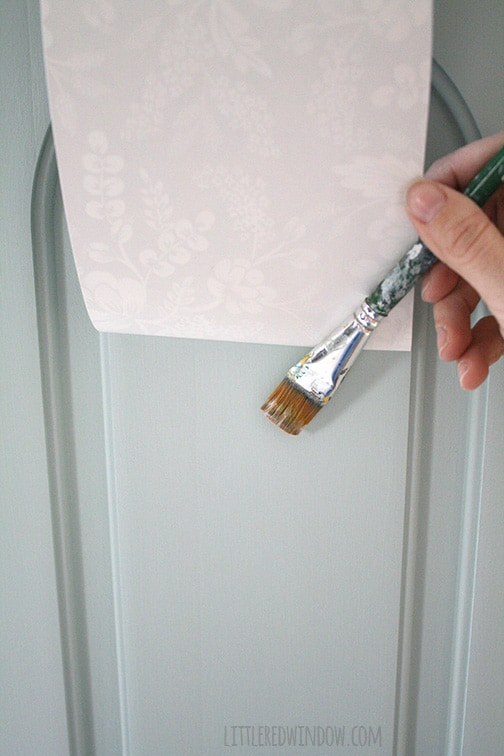 paintbrush applying mod podge to the cabinet door