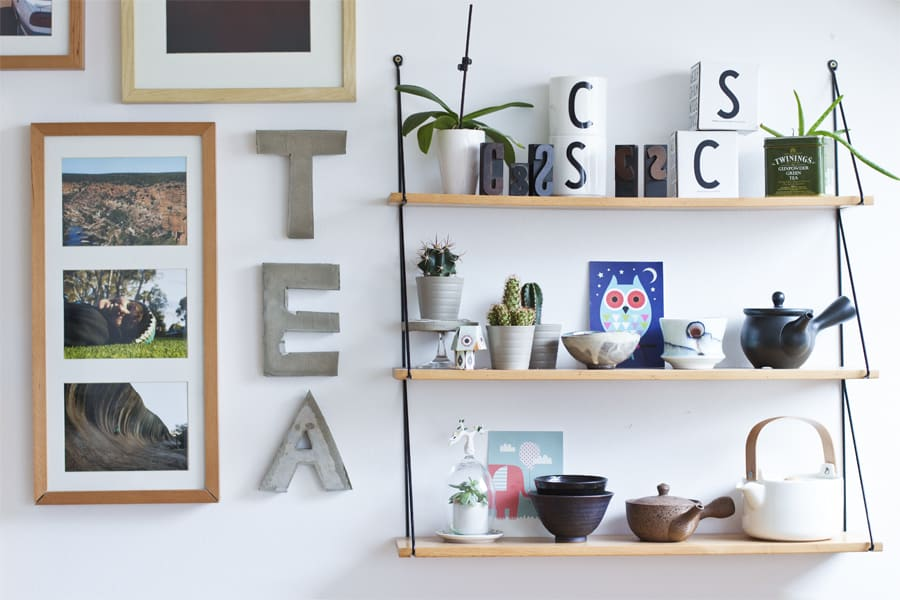 wall with art and shelves and three concrete letters vertically spelling TEA