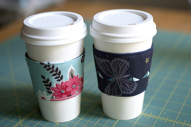 two travel coffee cups with floral fabric sleeves