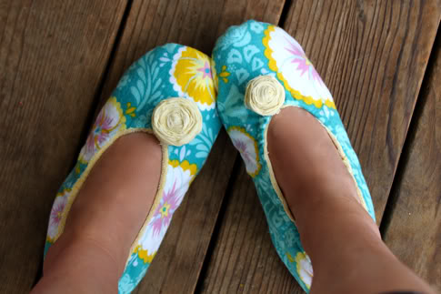 person's feet wearing teal fabric slippers