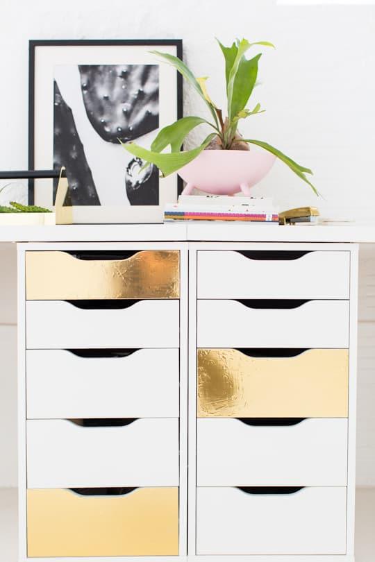 white dresser with three random drawers painted gold