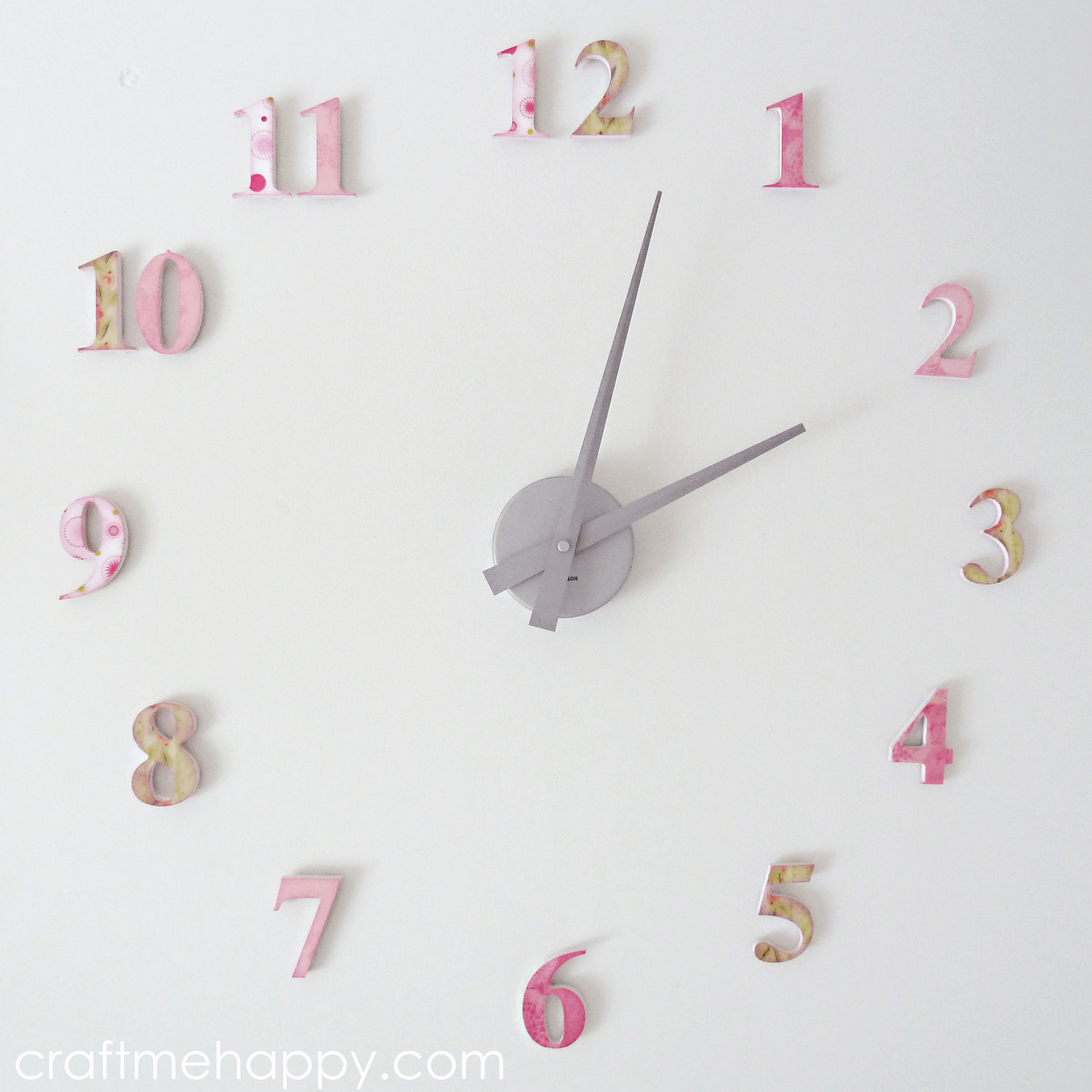 hand made nursery clock with wooden numbers decorated with scrapbook paper