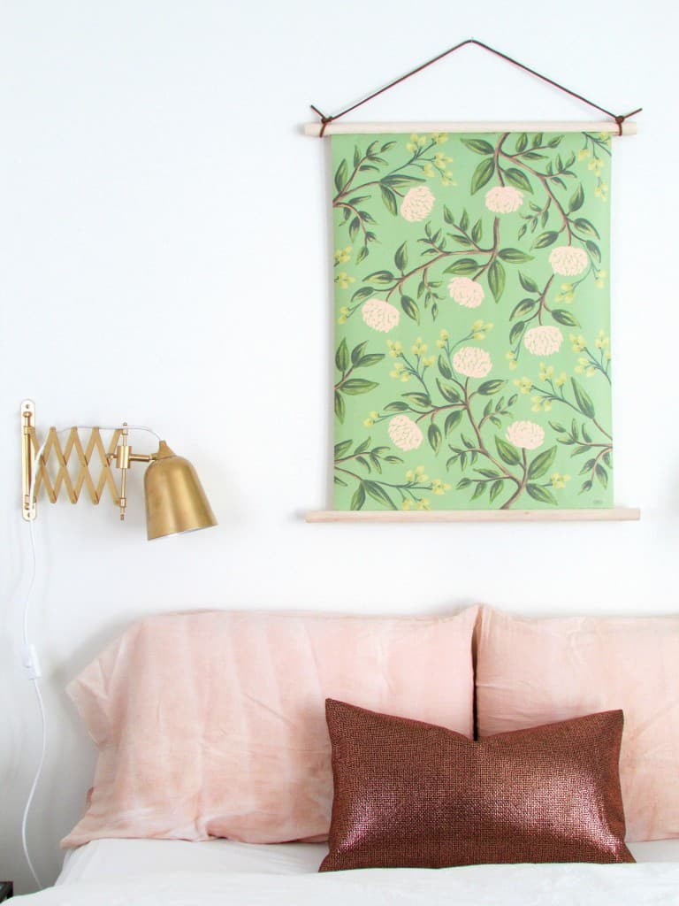 Sheet of floral wrapping paper with wood border used as wall art above a bed