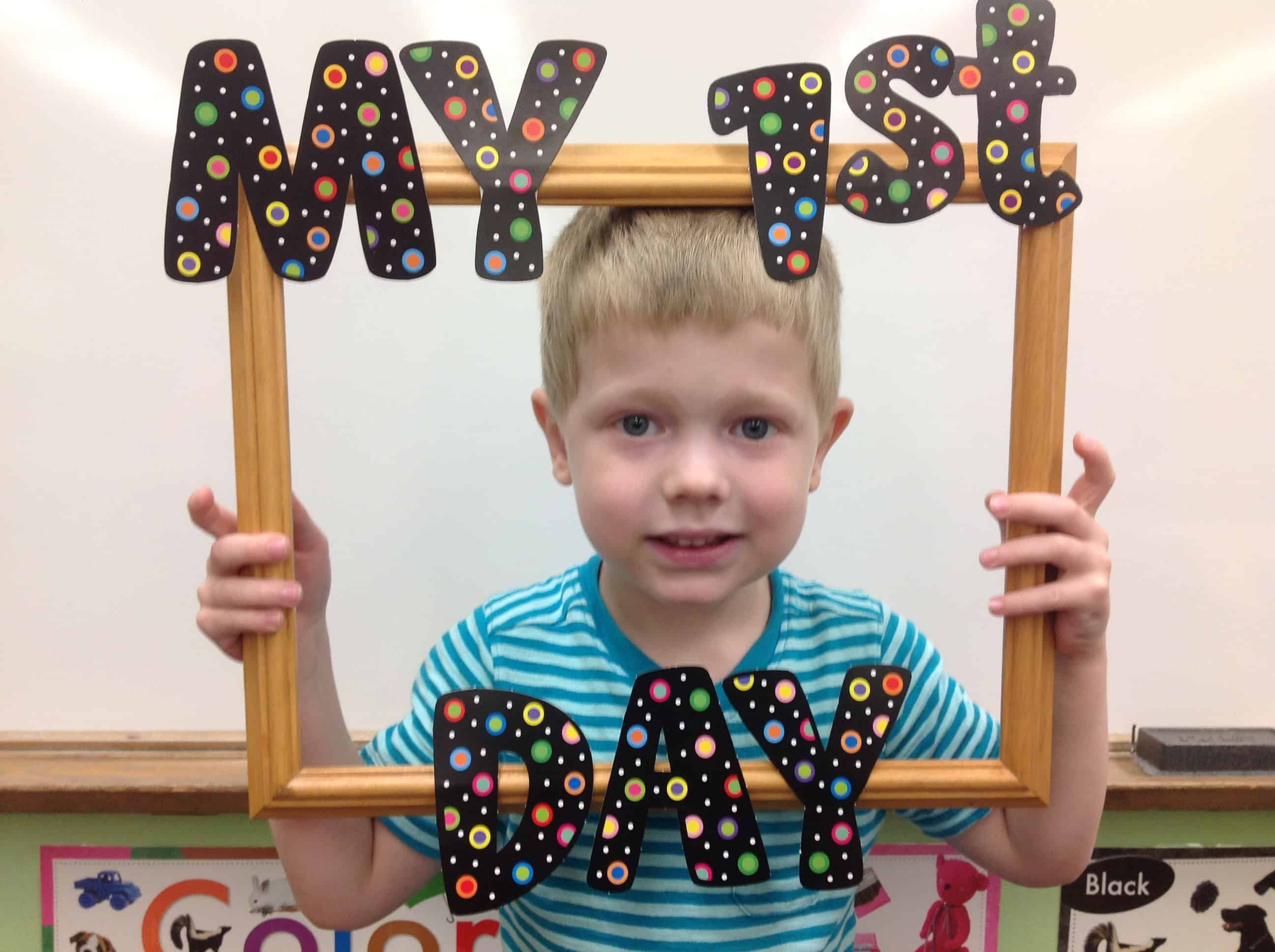 little boy holding frame that says my 1st day