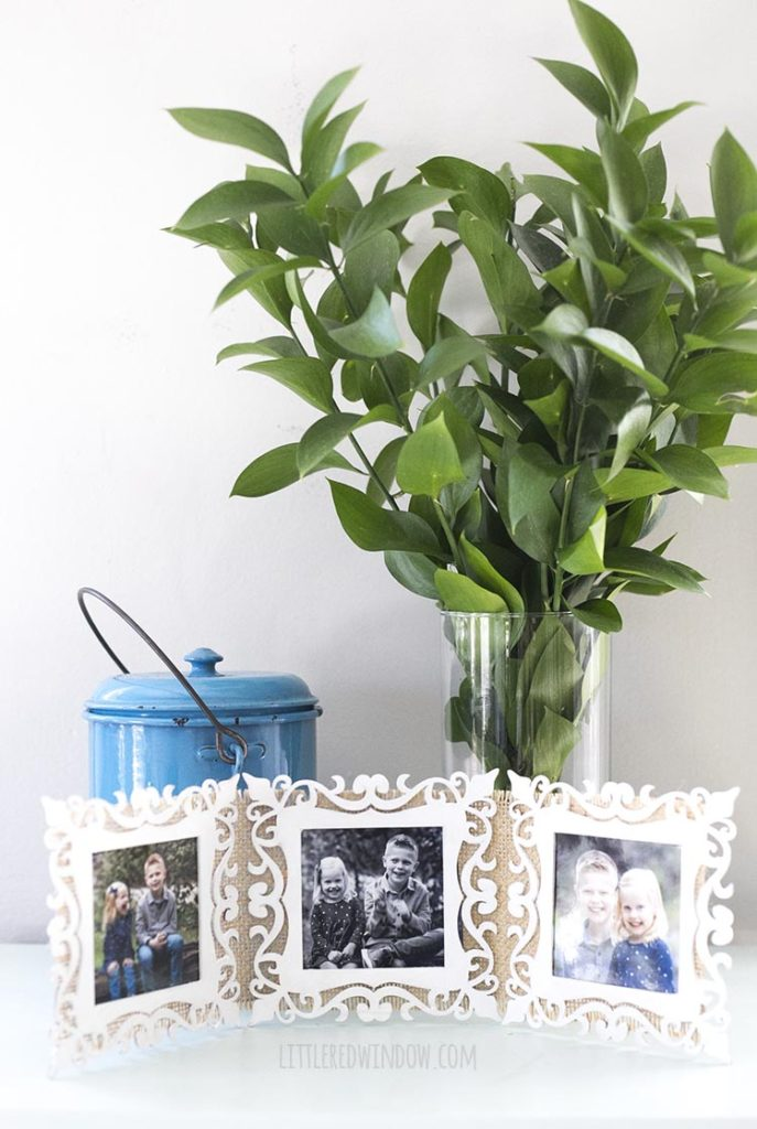 folding picture frame in front of a blue metal container and a vase full of greenery