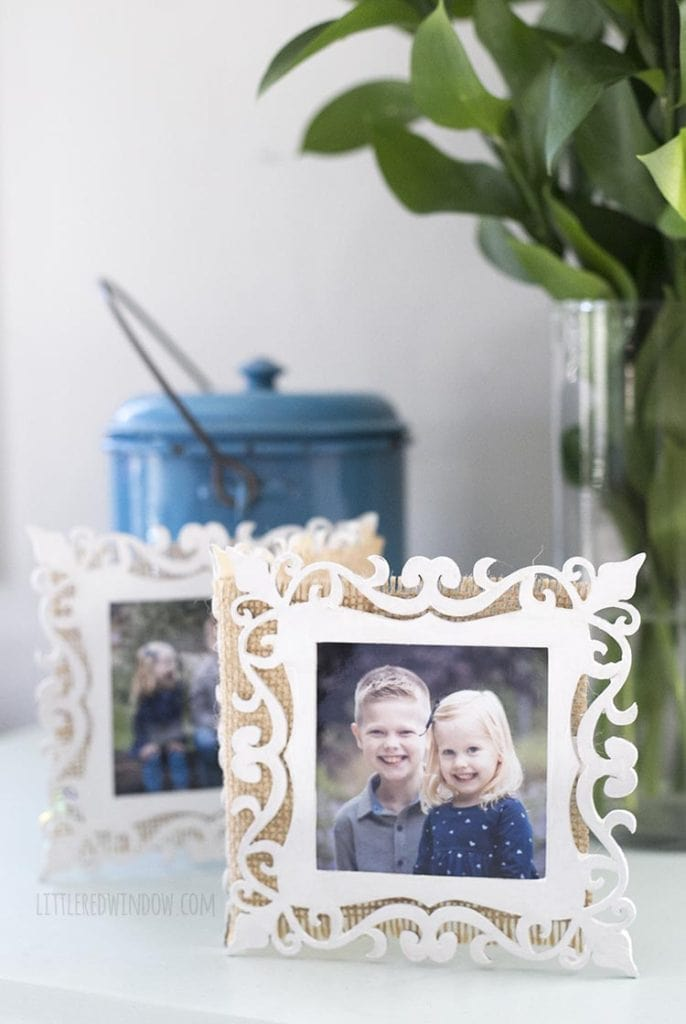 closeup of folding picture frame in front of a blue metal container and a vase full of greenery