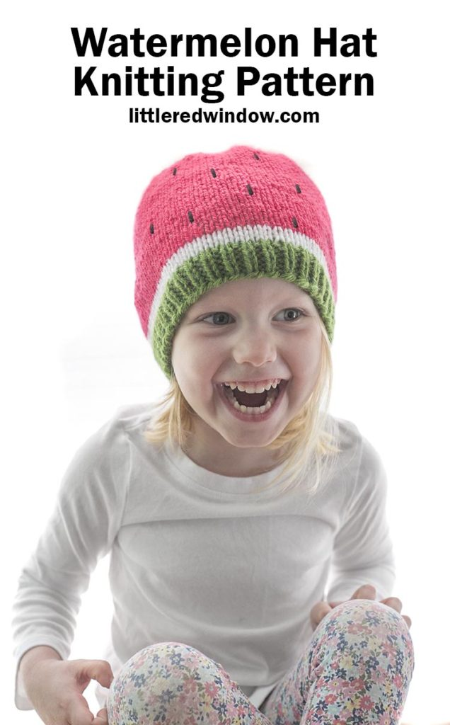 Little girl laughing and wearing a white shirt and green white and pink watermelon knit hat with black embroidered seeds