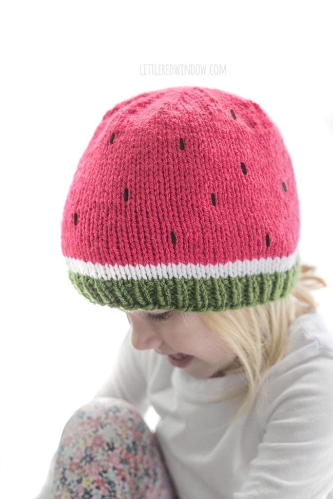 Little girl look down and to the left and wearing a white shirt and green white and pink watermelon knit hat with black embroidered seeds
