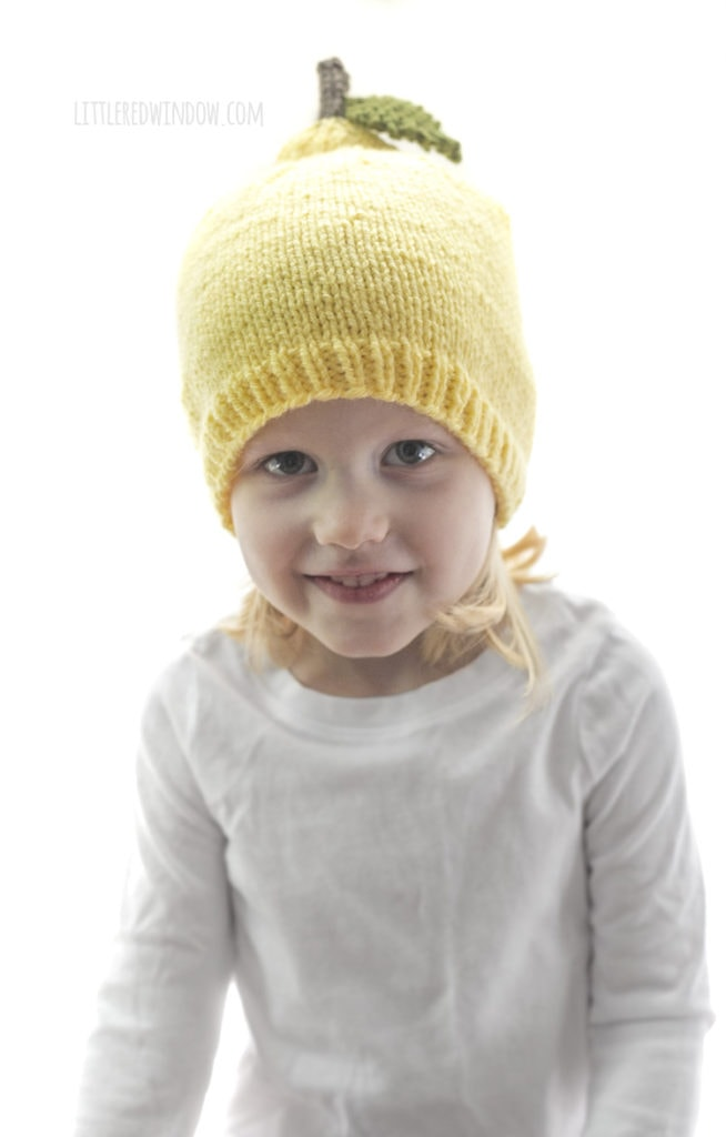 little girl wearing yellow lemon knit hat with stem and leaf and smiling at the camera