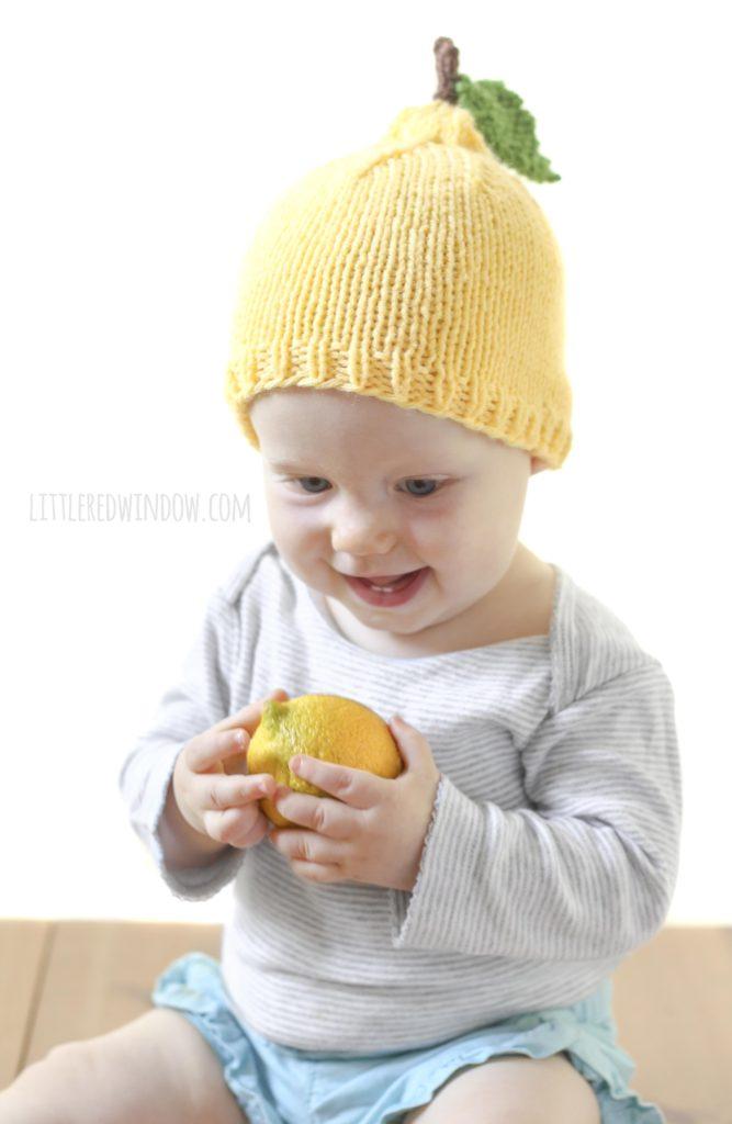 Baby holding a lemon and wearing a yellow knit lemon hat