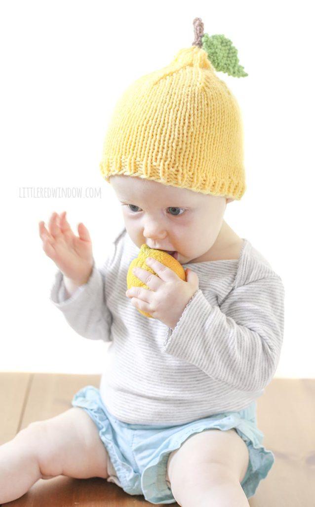 baby putting mouth on whole lemon and wearing a yellow knit lemon hat