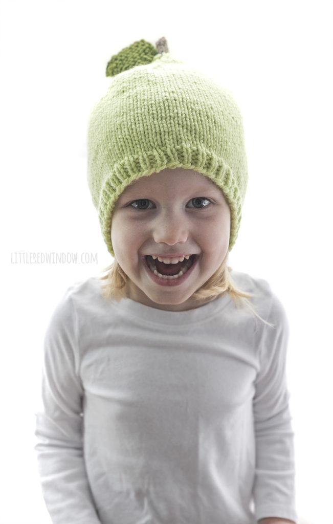 little girl laughing and wearing a green knit hat that looks like a pear with a stem and leaf