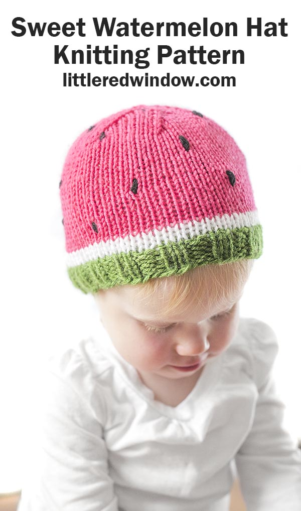 toddler playing with a toy and wearing a knit watermelon hat