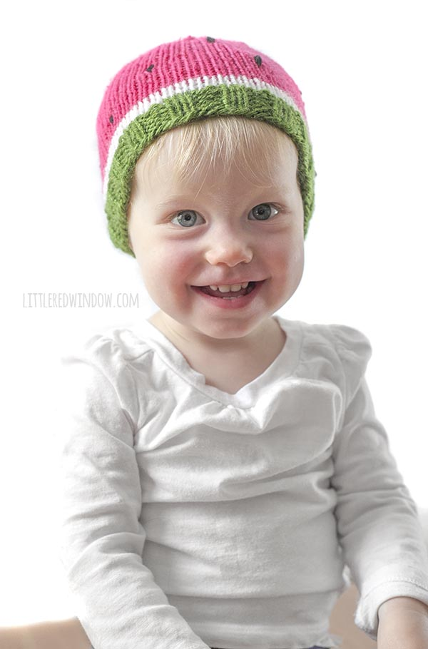 Smiling toddler in white shirt wearing knit watermelon hat