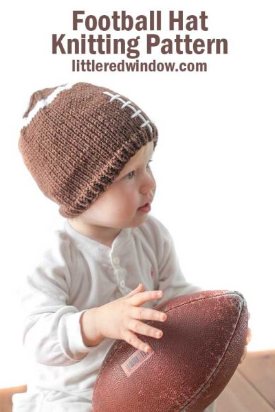 baby wearing brown knit hat that looks like a football and holding a real football in her lap looking off to the right