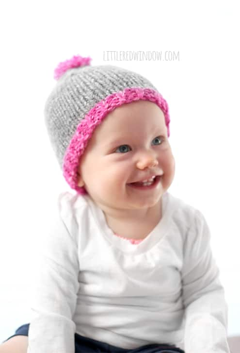 This little one is happy to donate hats to charity, they knit up super fast with the Do-Gooder free baby hat knitting pattern!