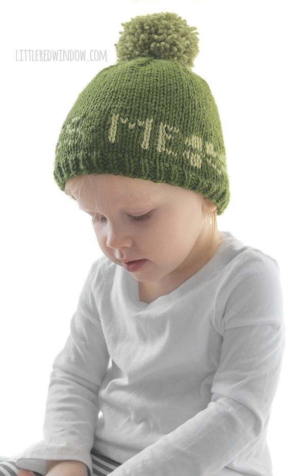 The cute toddler is showing off the St. Patrick's Day Kiss Me Hat knitting pattern in shades of green!