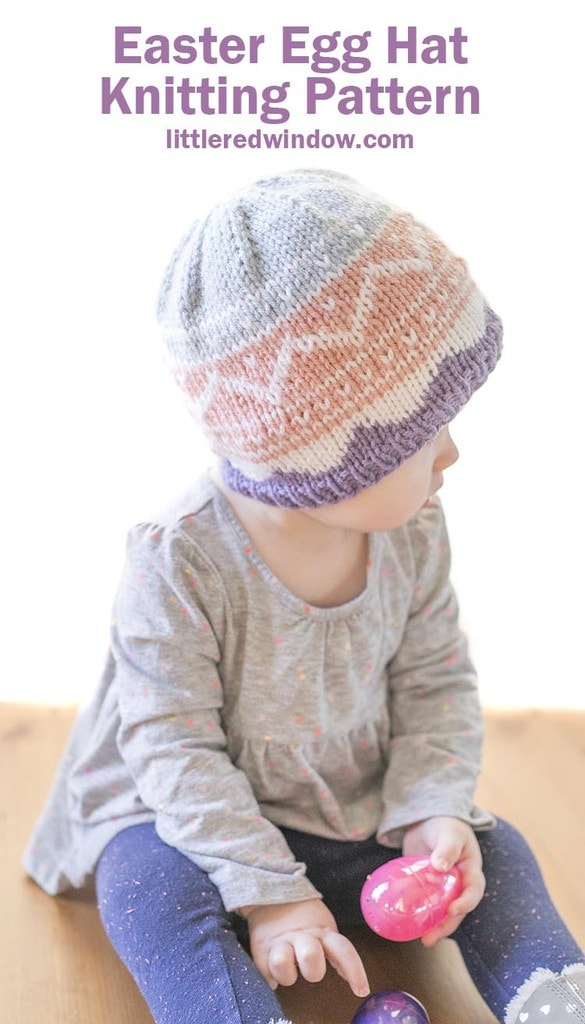 little girl wearing pink purple and blue easter egg patterned knit hat and looking off to the right