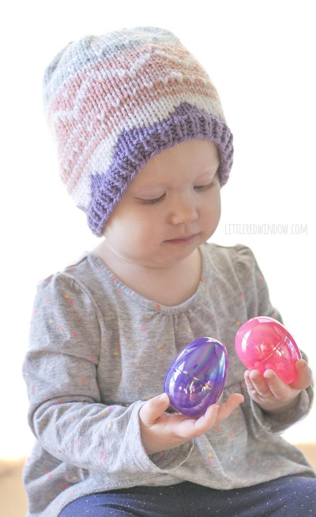 baby girl wearing knit easter egg hat and examining two pink and purple easter eggs in her hands