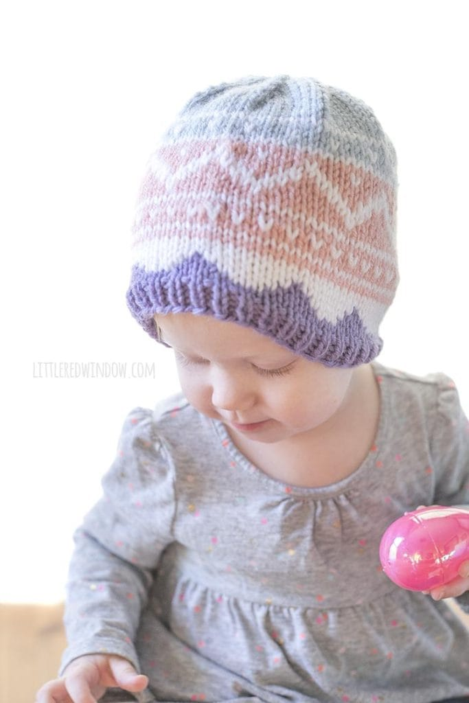 baby wearing knit easter egg hat and holding one pink easter egg