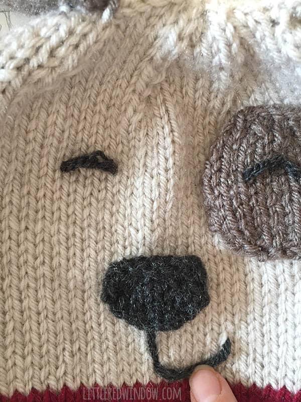 Hand stitching puppy mouth under nose on puppy dog hat