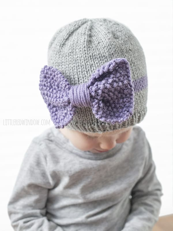 Closeup of seed stitch knit purple bow on the front of gray knit baby hat