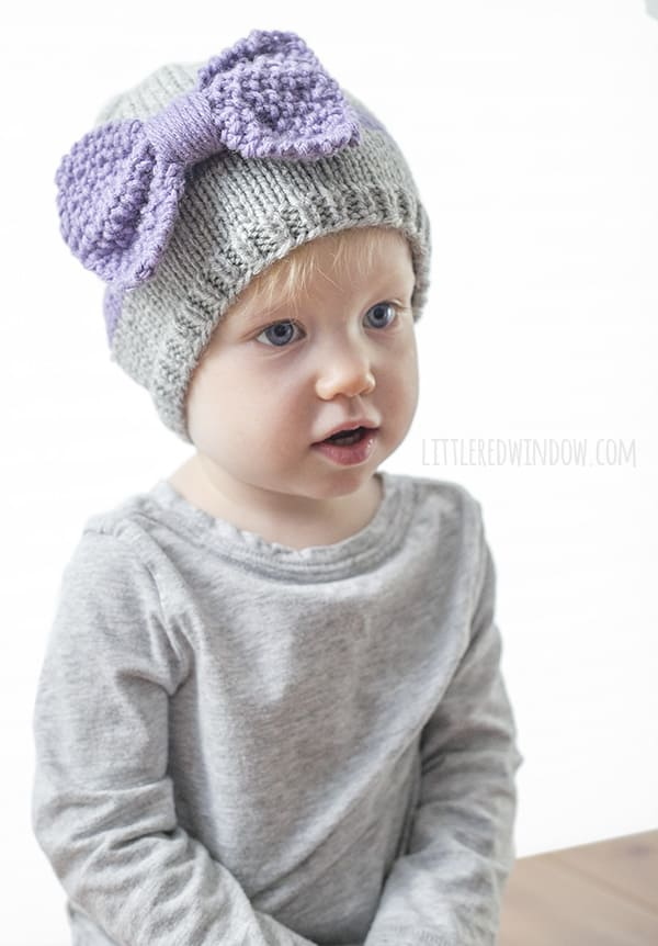 Toddler wearing a gray shirt and a gray knit hat with large lavender knit bow on the front