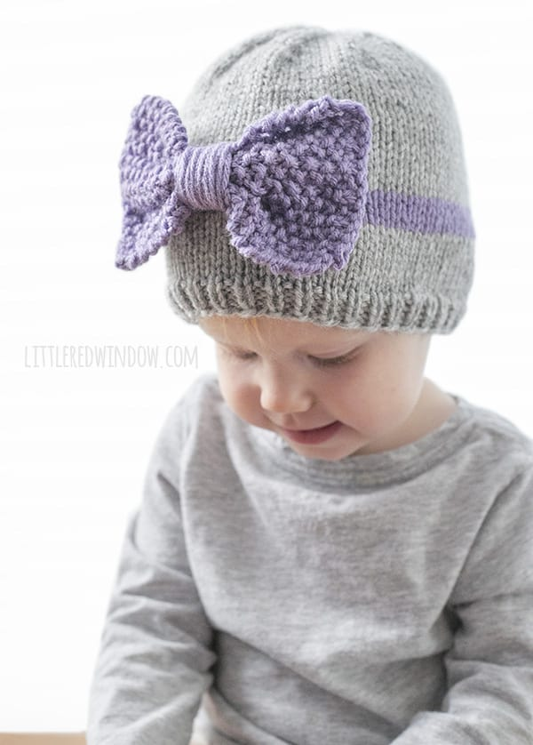 Toddler looking down and wearing a gray knit baby hat with large light purple knit bow on the front of it