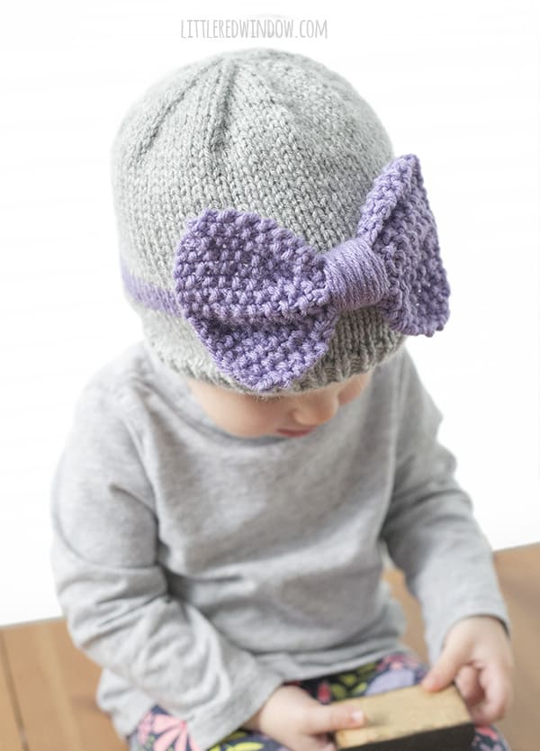 Top view of toddler wearing gray knit baby hat with large purple knit bow on the front