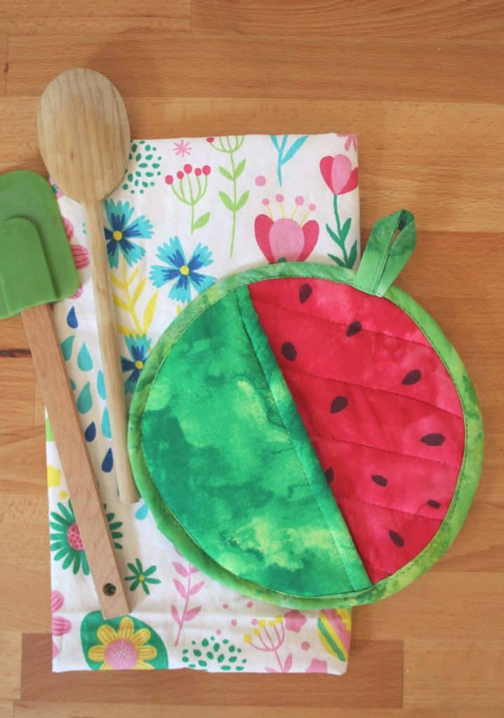 Round green potholder with one half painted red to look like watermelon on top of a tea towel and spatulas