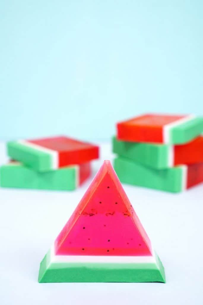 Triangle wedge of green white and red watermelon soap with more soap stacked in the background.