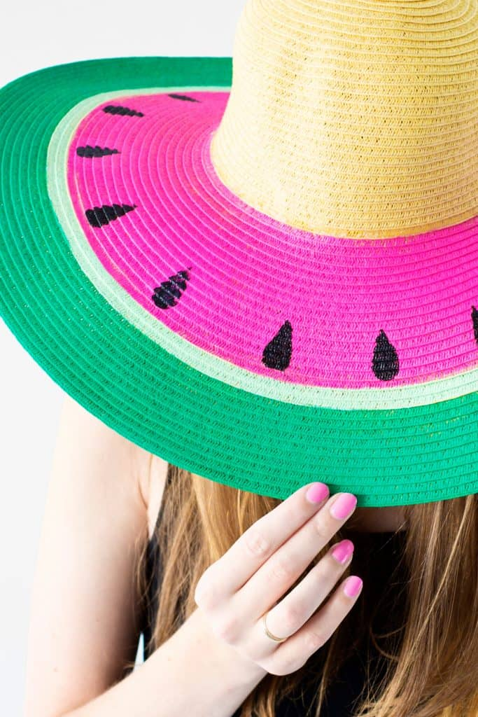 Straw sun hat with the brim painted with green white and pink stripes and black seeds to look like a watermelon