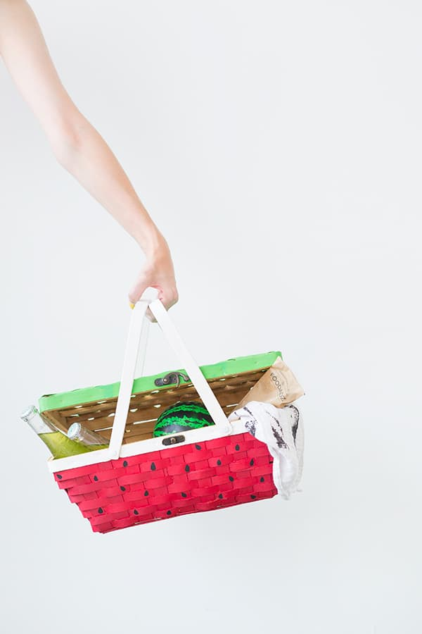 Womans arm holding wicker picnic basket with green painted lid and pink painted bottom with black seeds