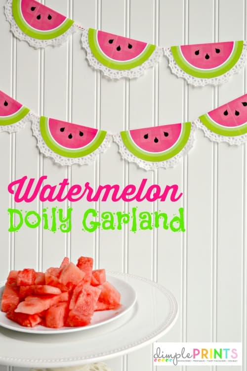 Hanging garland made from half circle doilies with the centers painted to look like watermelon slides in front of a white wall