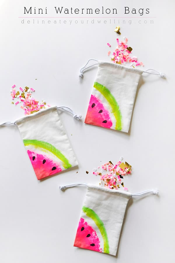 Small drawstrings bags painted with watermelon wedges on the corner and pink confetti spilling from the bags