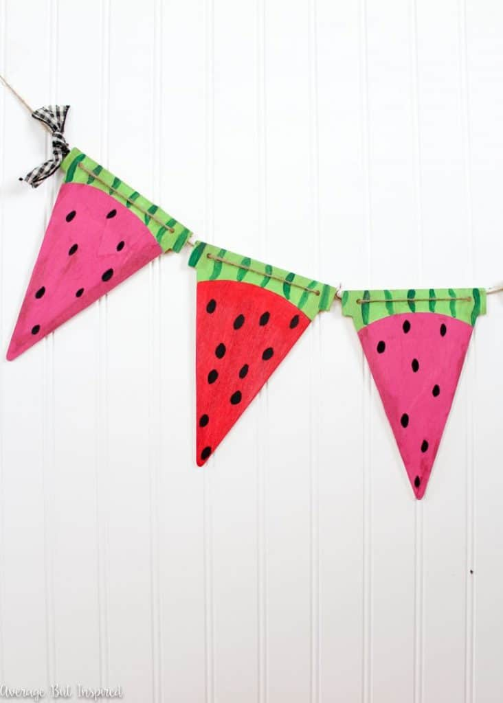 Cute triangle bunting painted to look like watermelon slices hanging in front of a white wall